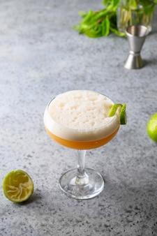 Pisco zure cocktail van whisky, limoen op grijs.