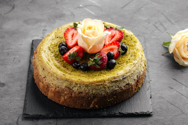 Pistache-cheesecake gegarneerd met bessen en roos