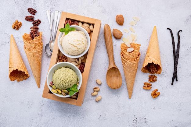 Pistache en vanille-ijs in kom met gemengde notenopstelling op witte steenachtergrond