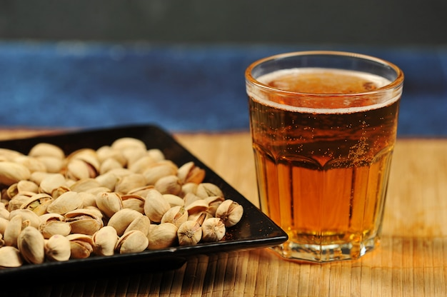 Pistaches in een bord en een glas bier