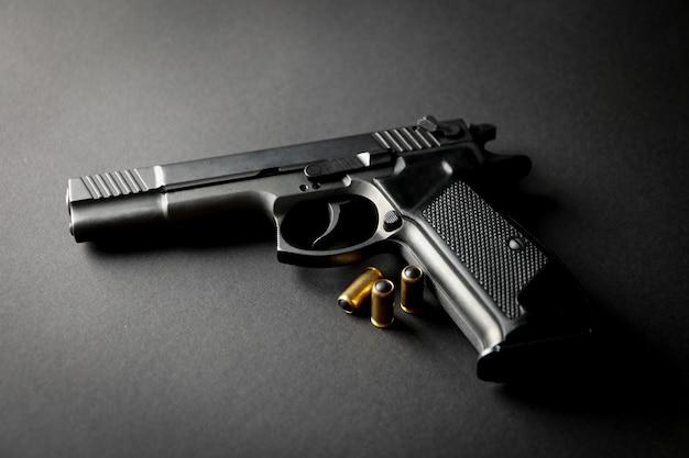 Pistool en traumatische kogels op zwart. zelfverdedigingswapen