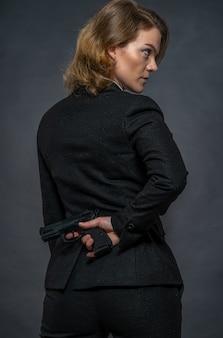 Pistool in de hand achter de rug van een vrouw in een pak