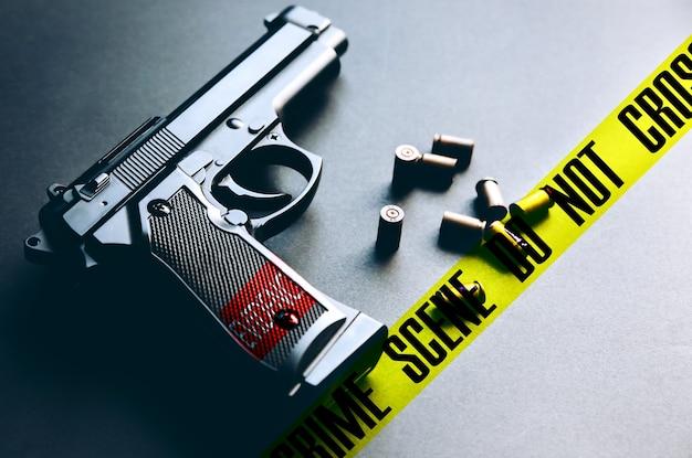 Pistool met kogels op tafel liggen. legaliseren van wapens. plaats delict kruist de tape niet.