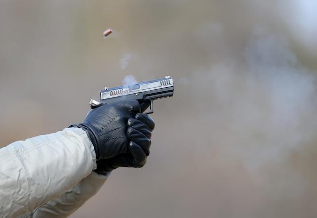 Pistoolschieten met twee handen, de granaten die uit de sluiter komen en blauwe rook.