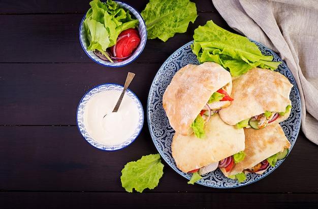 Pita gevuld met kip, tomaat en sla en yoghurtsaus