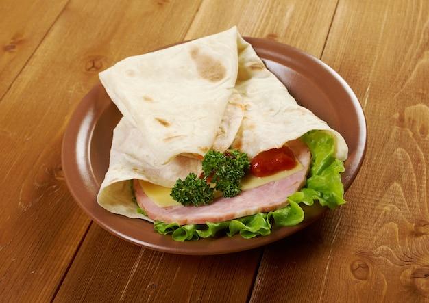 Pita sandwich met kaas, ham, peterselie en tomatensaus