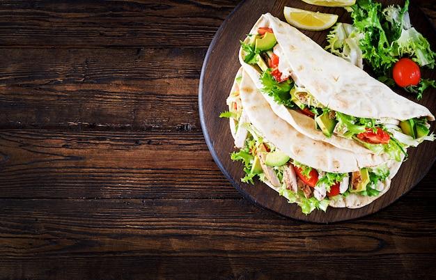 Pitabroodjesandwiches met gegrild kippenvlees, avocado, tomaat, komkommer en sla geserveerd op houten achtergrond.