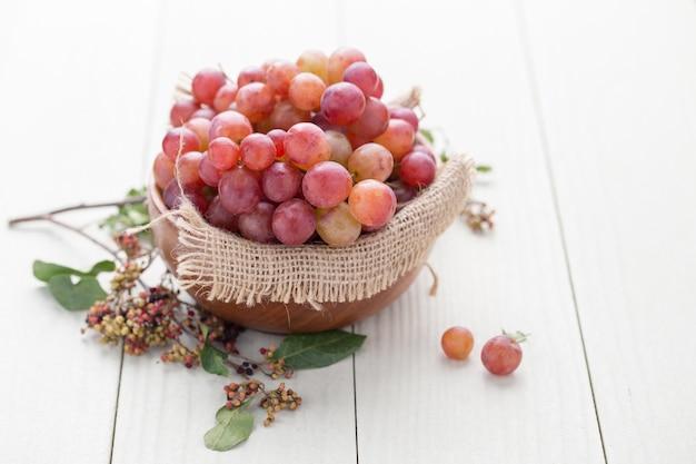 Pitloze druiven in een houten kom op een witte houten vloer.