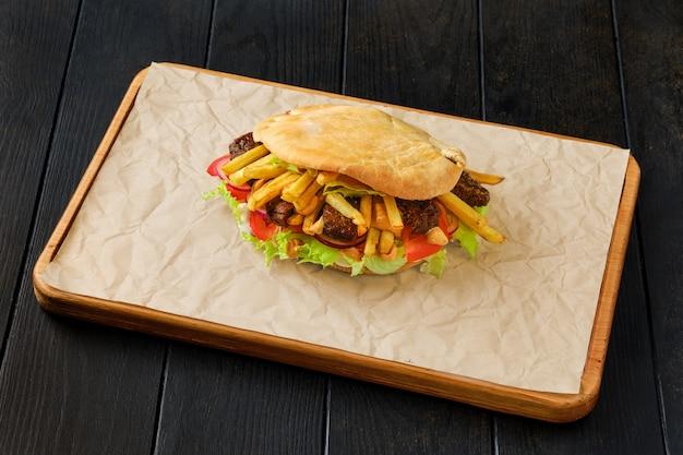 Pittabrood gevuld met salade, tomaat, ui, frietjes en lamsvlees op houten plank