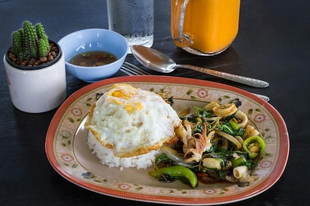 Pittig gebakken basilicumblad met zeevruchten en rijst op zwarte lijstachtergrond