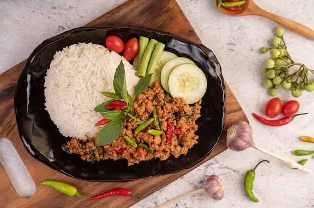 Pittig gehakt varkensvlees en rijst op een zwarte plaat.