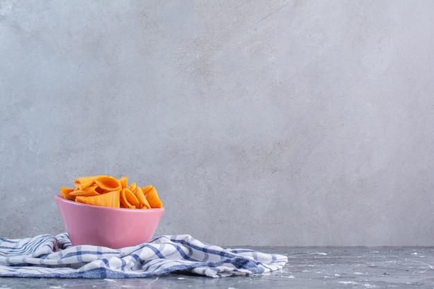 Pittige aardappelchips in kom op theedoek, op het marmeren oppervlak