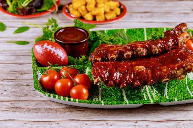 Pittige barbecue spareribs met tomaten voor een voetbalfeestje. horeca-industrie.