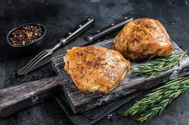Pittige bbq gegrilde kippendijen op een houten bord met rozemarijn. bovenaanzicht.