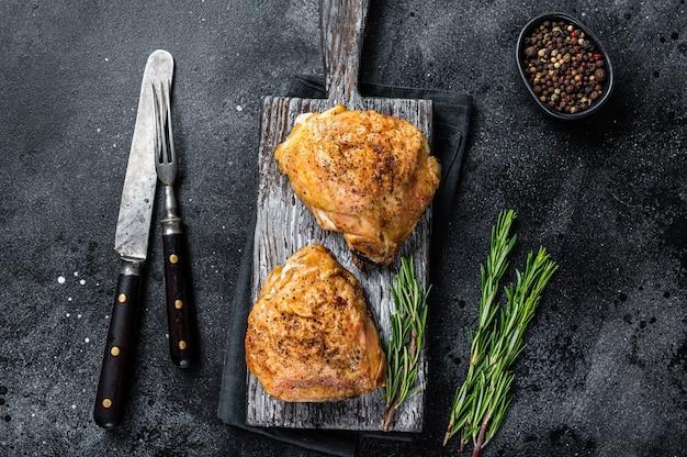 Pittige bbq gegrilde kippendijen op een houten bord met rozemarijn. zwarte achtergrond. bovenaanzicht.