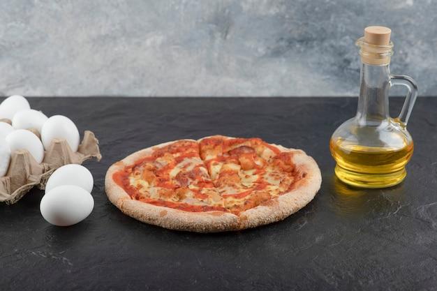 Pittige buffel kip pizza, olie en rauwe eieren op zwarte ondergrond.