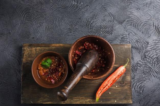 Pittige chili op een donkere achtergrond in keramische platen op een houten bord