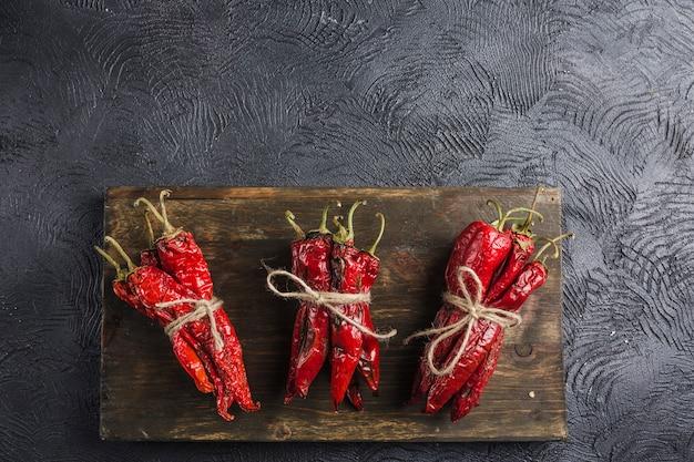 Pittige chili op een donkere achtergrond op een houten bord