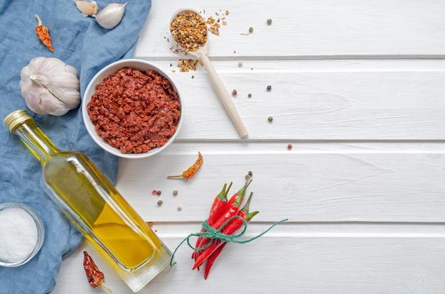 Pittige chili op een lichte achtergrond, flatlay. gebruikt als ingrediënt voor harissa, ajika, muhammara. roodgloeiende spaanse peper, zout, knoflook, olijfolie. oost- en midden-oosten keuken.