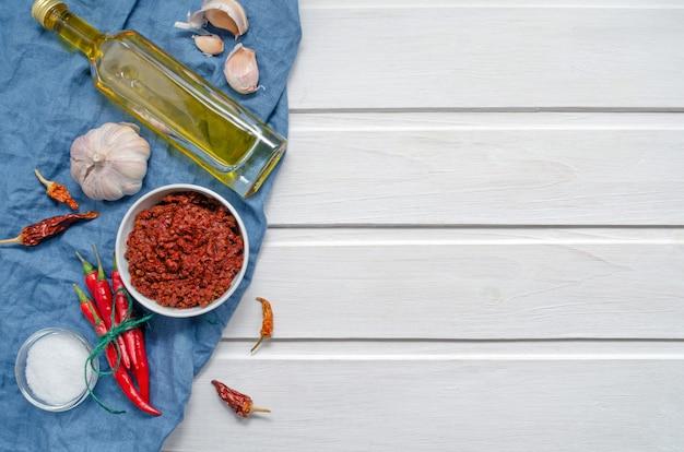 Pittige chili op een lichte achtergrond, flatlay. gebruikt als ingrediënt voor harissa, ajika, muhammara. roodgloeiende spaanse peper, zout, knoflook. oost- en midden-oosten keuken. kopieer ruimte.