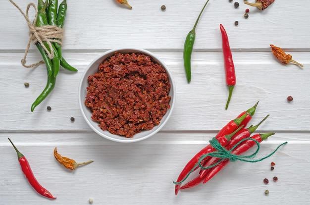 Pittige chili op een lichte tafel, flatlay. gebruikt als ingrediënt voor harissa, ajika, muhammara. oost- en midden-oosten keuken.