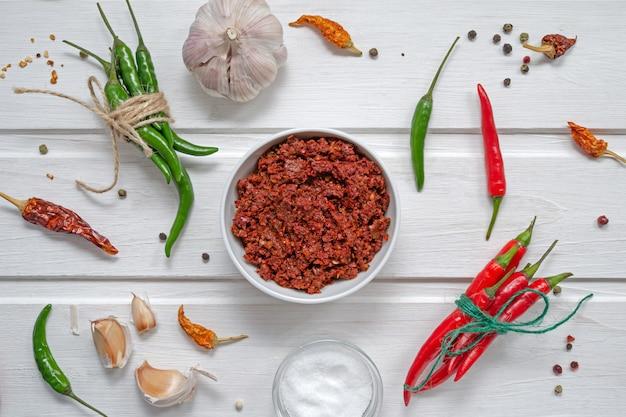 Pittige chili op een lichte tafel, flatlay. gebruikt als ingrediënt voor harissa, ajika, muhammara. roodgloeiende spaanse peper, zout, knoflook. oost- en midden-oosten keuken.