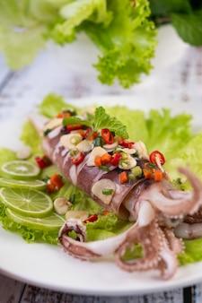 Pittige citroen inktvis met laos, pepers, wortelen, pepermunt, lente-uitjes en knoflook op een plaat op een witte houten vloer.