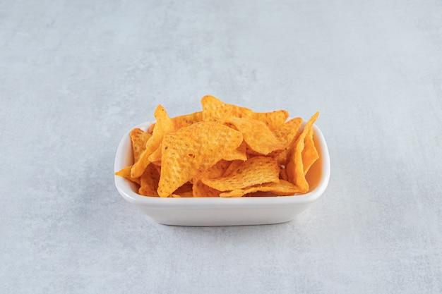 Pittige driehoekige chips in witte kom op steen.