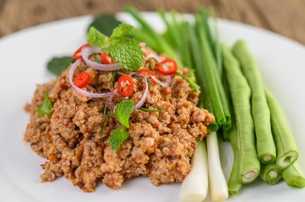 Pittige gehakt varkens salade op een witte plaat met linzen, kaffir limoen bladeren en lente-uitjes.
