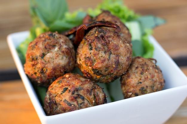 Pittige gehakt varkensvlees ballen met salade in een witte plaat op de tafel. thais eten (larb moo tod)