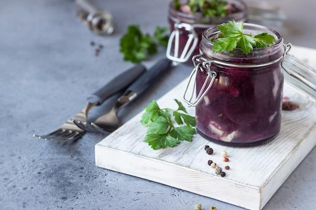 Pittige gesneden haring in rode wijnmarinade geserveerd in een glazen pot.