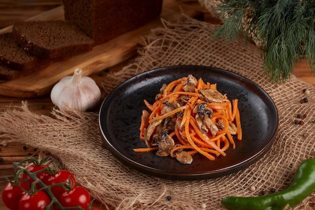 Pittige ingelegde wortel en champignonsalade op een plaat. houten.