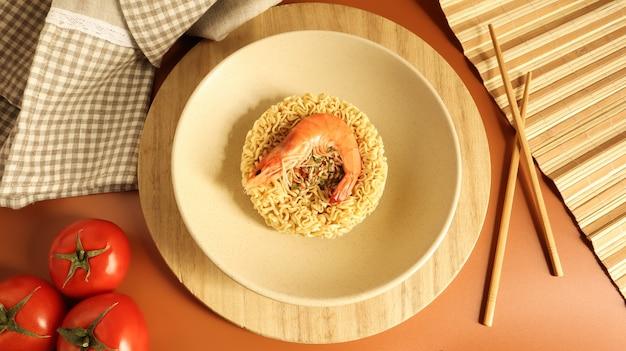 Pittige instant noedelsoep met garnalen en groenten. garnalensoep, koken, eten. rauwe gedroogde cirkelvormige vermicelli in een bord. pasta, voor de bereiding waarvan het voldoende is om kokend water te gieten.