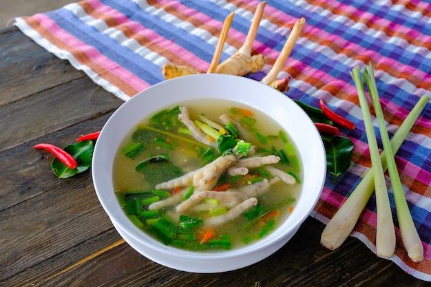 Pittige kip benen soep in witte kop op houten tafel