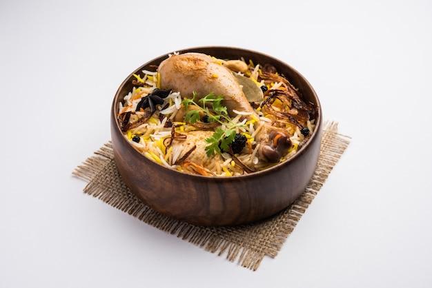 Pittige kip biryani in restaurantstijl in houten kom met raita en salan, populair indiaas of pakistaans eten
