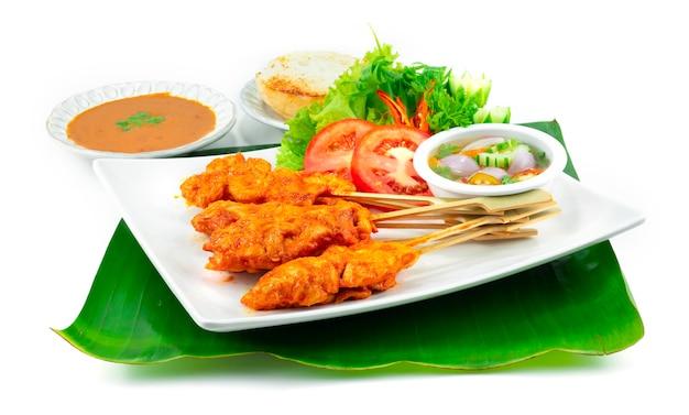 Pittige kip saté of pittige gegrilde kip in spiesjes geserveerd gegrild brood dompelen chili pinda saus, zoetzure saus thais eten voorgerecht schotel decoratie met gesneden groenten zijaanzicht