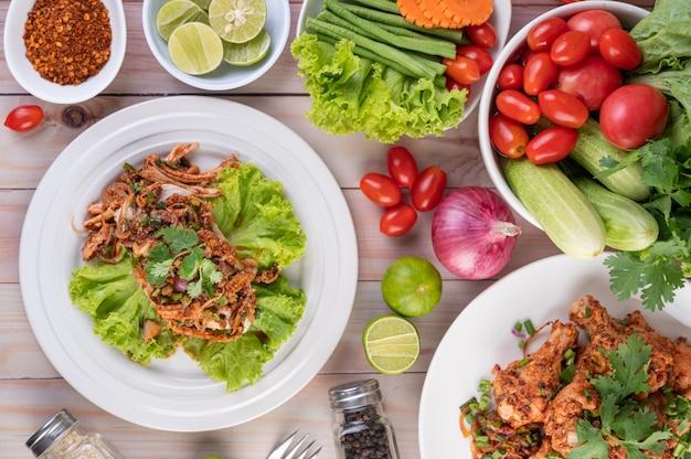 Pittige kipgehakt op een wit bord compleet met komkommer, sla en bijgerechten.