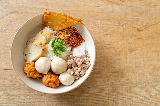 Pittige kleine platte rijstnoedels met visballetjes en garnalenballetjes zonder soep - asian food style