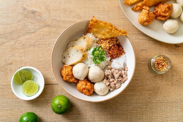 Pittige kleine platte rijstnoedels met visballetjes en garnalenballetjes zonder soep - aziatisch eten