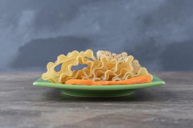 Pittige lasagnebladen naast fijngehakte wortelen op het bord, op het marmer.