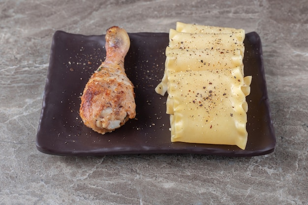Pittige lasagnevellen naast kip drumstick op de houten plaat, op het marmer.