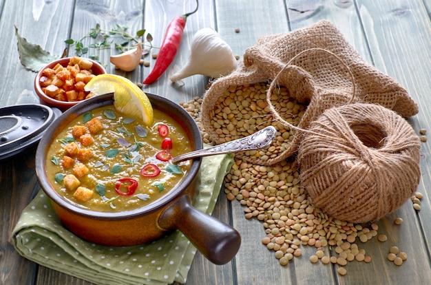 Pittige linzensoep met chili, knoflook en ui op houten tafel