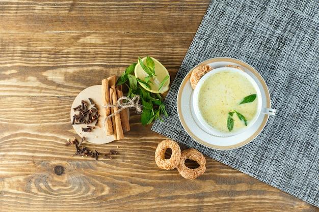 Pittige melk in een kopje met munt, koekjes, kruidnagel, citroen, kaneelstokjes bovenaanzicht op houten tafel