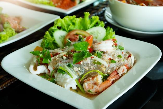 Pittige noedelsalade, pittige vermicellisalade met verse garnalen en inktvis, thaise voedselstijl.
