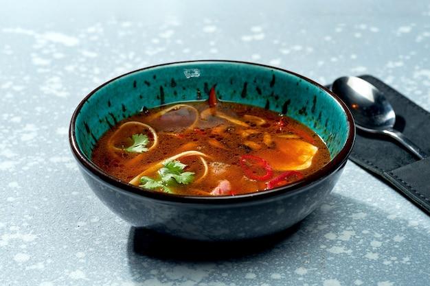 Pittige pan-aziatische ramensoep met noedels, vlees, hete pepers en koriander in een blauwe kom op een grijze ondergrond