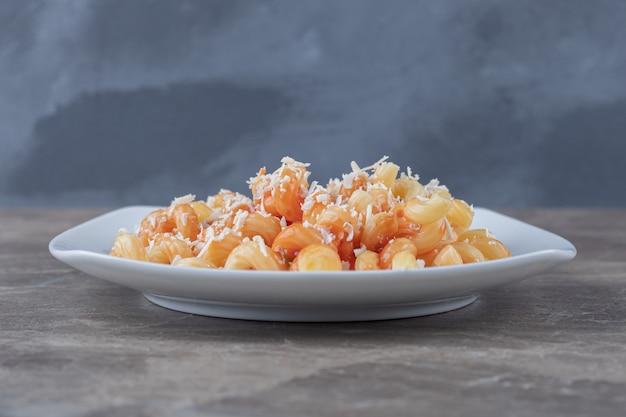 Pittige pasta met tomatensaus, op het marmer.