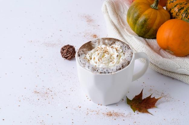 Pittige pompoen latte met romig schuim, blad en oranje pompoen op witte plaat, kopieer ruimte