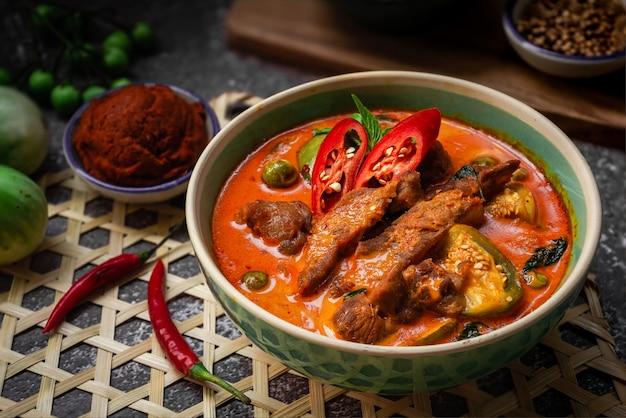 Pittige rode curry met varkensvlees - thais eten gebaseerd op koken op rode currypasta en thaise lokale kruiden