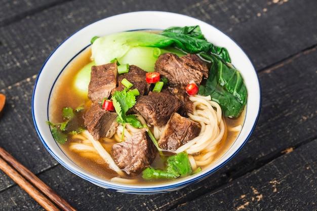 Pittige rode soep beef noodle in een kom op houten tafel