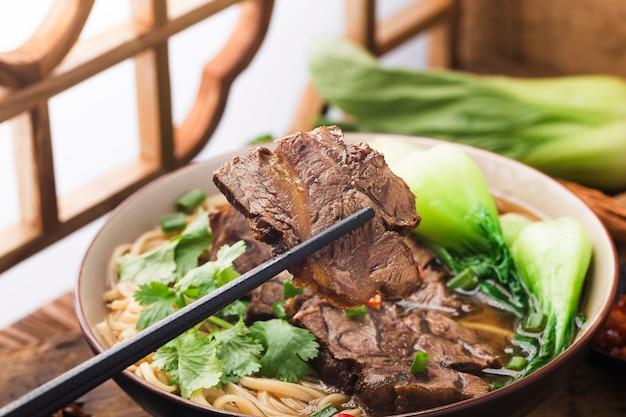 Pittige rode soep rundvleesnoedel in een kom op houten tafel